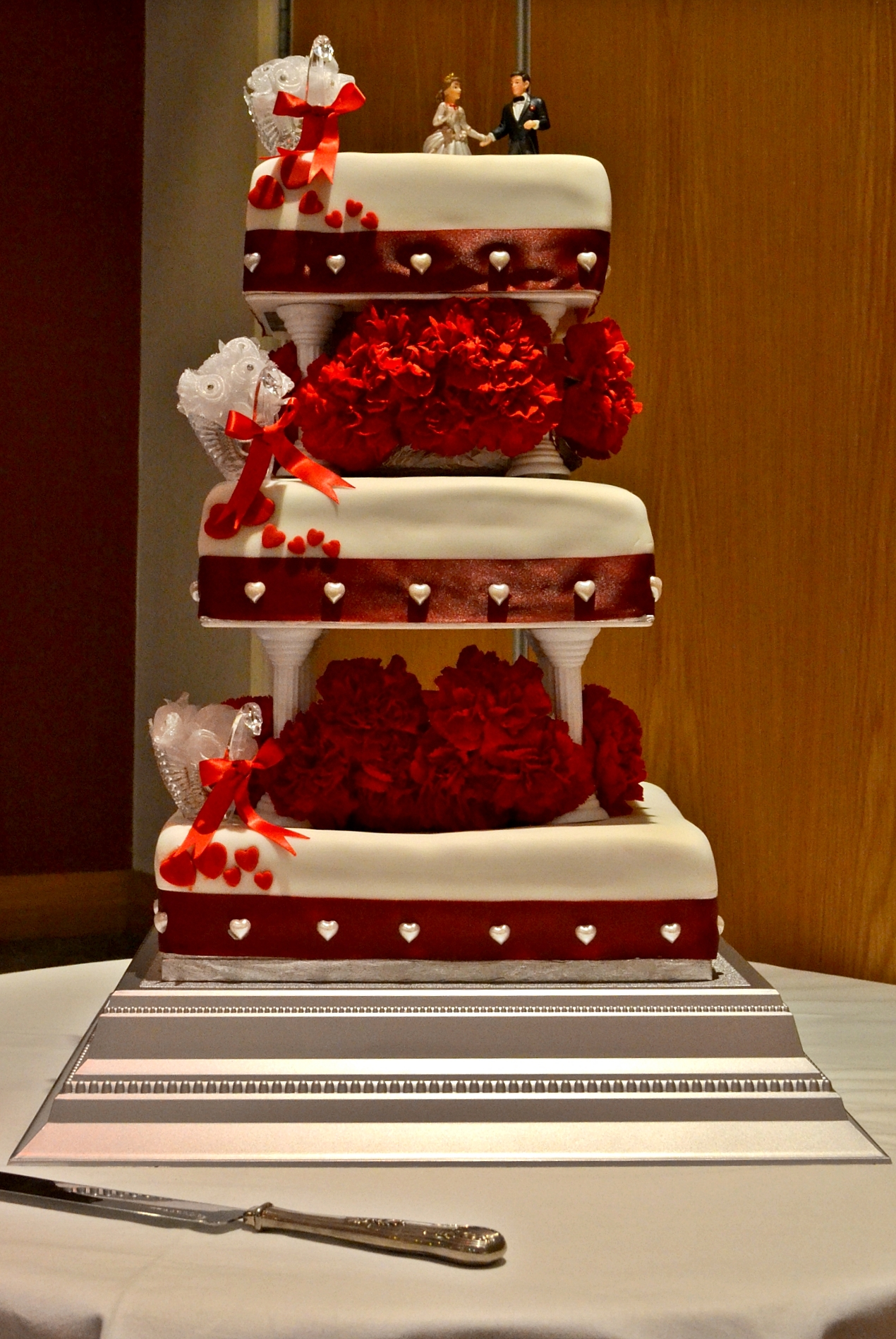 Les Plaisirs 3-tier square wedding cake with red carnations