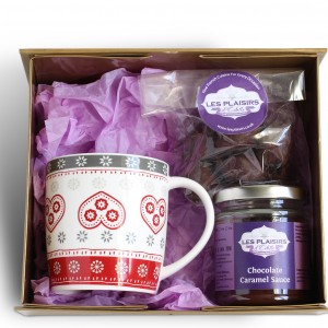 Gift box with mug, dessert sauce and chocolate truffles